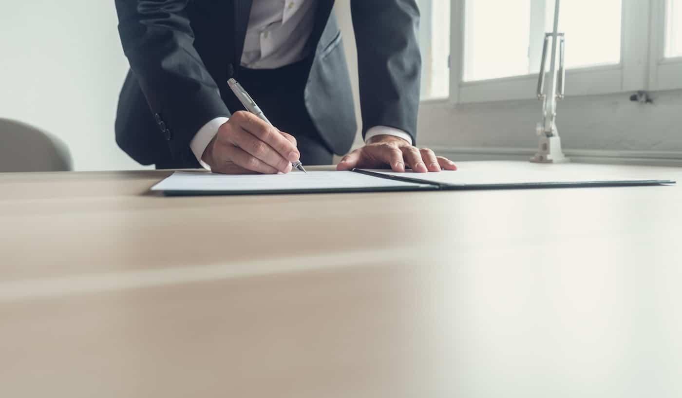 man signerar avtal för att starta kommanditbolag